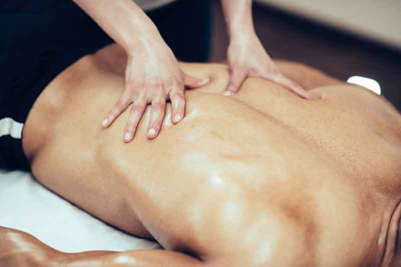 Massage therapist massaging lower back region of a male athlete
