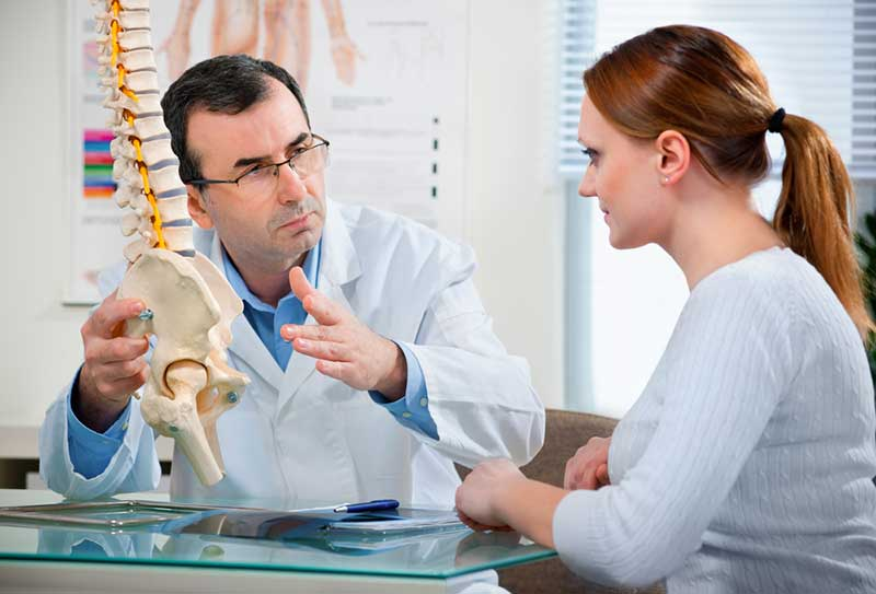 Physical Therapist shows the problem areas on the model of the spine to the patient and explains the cause of her pain