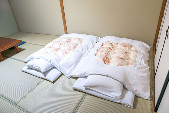 Futon a Japanese quilted mattress rolled out on the floor for use as a bed